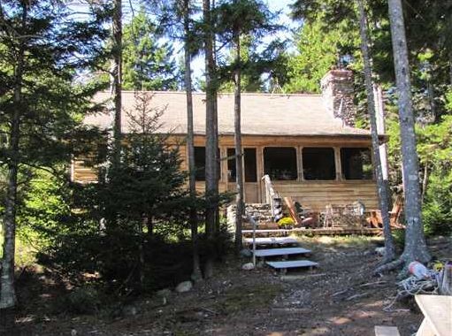 Real Estate Listing - DeerIsle Maine log home with a stone fireplace on tidal ocean cove